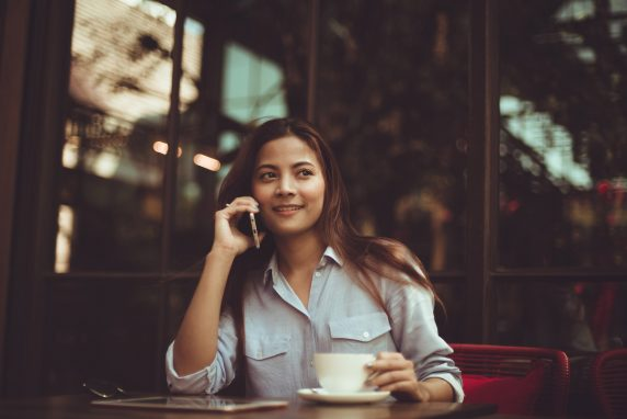 Woman drinking coffee listening to music on hold