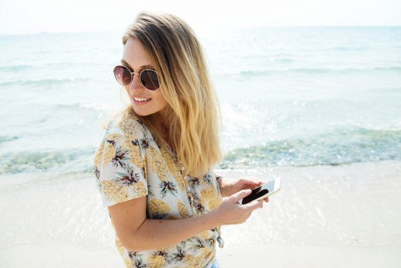 Lady on beach using her phone whilst roaming